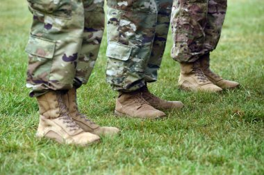 US soldiers legs in green camouflage military uniform. US troops