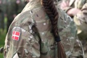 Woman soldier. Woman in army. Flag of Denmark on soldiers arm.