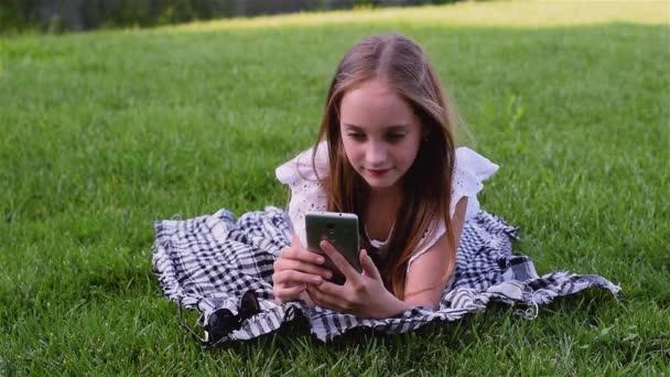 Krásná mladá dívka pomocí telefonu leží na trávě v parku