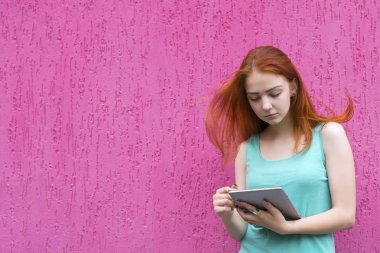 Redhead girl using tablet pc