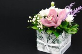 Růžové a bílé květy v poli z krajky s bílou vázankou na černém pozadí