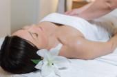 Fotografia Chiuda in su della giovane bella donna che si trova e che riceve massaggio al salone di bellezza spa