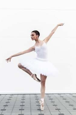 Beautiful young ballerina doing the attitude pose with a white tutu.