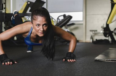 Attractive young woman doing push-ups at gym.