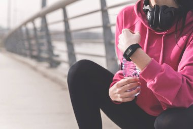 Cropped view of female hands holding bottle of water and sports watch