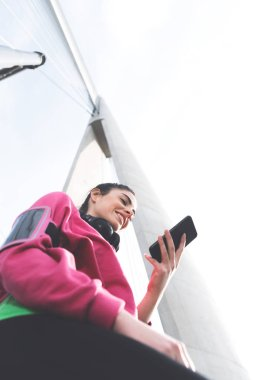 View from below of pretty young sporty girl in sportswear holding mobile phone and searching online for tracking miles app
