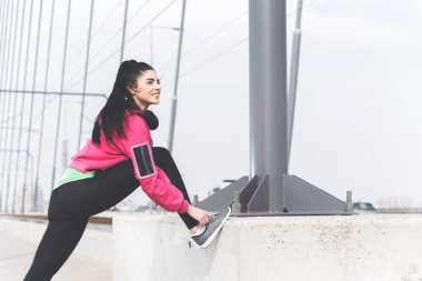 Attractive young woman in sportswear stretching and getting ready for street workout