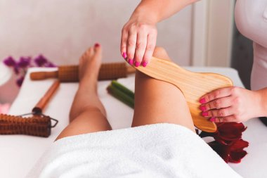 Closeup legs of beautiful young lady on maderotherapy anticellulite massage treatment
