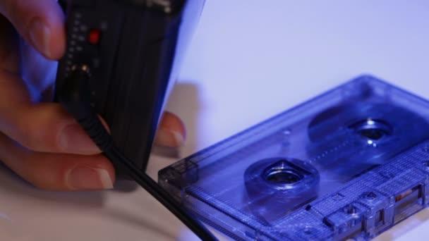 Žena ruce položte kompaktní hudební magnetofonové pásky v staré retro přenosný přehrávač - detailní na prsty a walkman, naklonění fotoaparátu nahoru