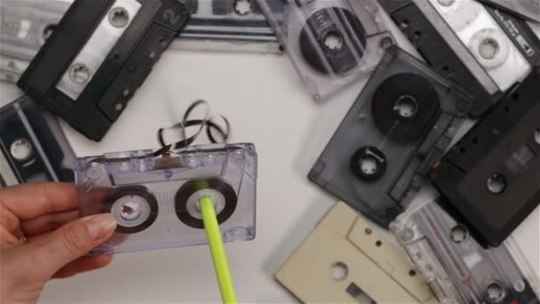 Žena rukou naviják pásku zpět v audio kazeta pomocí pera - společné oprava vadného hráče funkce, pohled shora, closeup