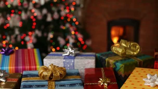 viele Weihnachtsgeschenke vor dem Kamin und verschwommenes Licht am Weihnachtsbaum am Abend - Kamera rutscht langsam