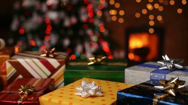 Weihnachtsgeschenke vor dem Kamin und verschwommenes Licht am Weihnachtsbaum am Abend - Kamera schließt auf dem verschwommenen Speck