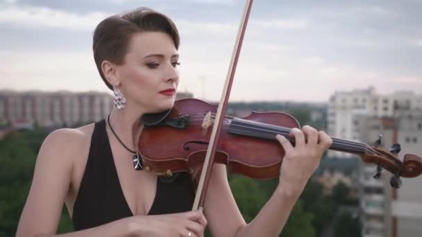 Gyönyörű fiatal nő játszik a hegedű, a tetőn.