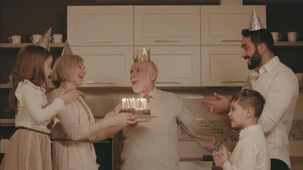 Rodina slaví narozeniny dědové. Starší muž sfoukne svíčky na dortu