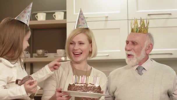 Starší muž sfoukne svíčky na dortu