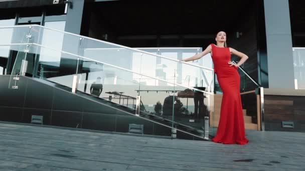 schöne Mädchen in rotem formalen Kleid posiert auf der Straße an einem sonnigen Tag.
