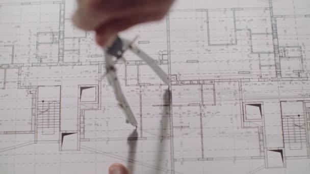 junger Architekt zeichnet eine Zeichnung auf Papier. Nahaufnahme.