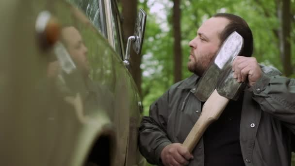 Slow Motion Of Casual Strong Man Has Shave with Ax near Classic Car in Wild Deciduous Forest.