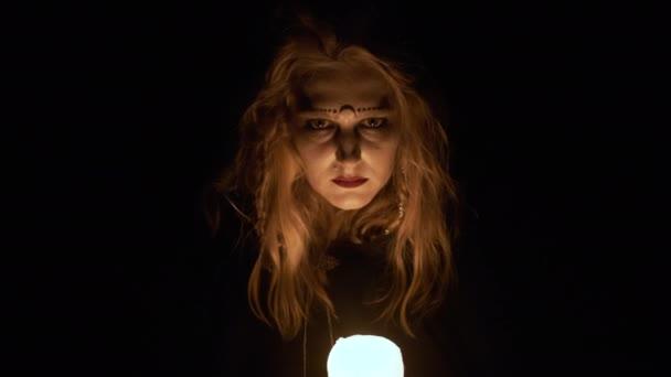Halloween kép. Fiatal Boszorkány portréja. A boszorkány gyertyát tart a kezében..