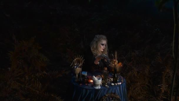 Halloween Image. Mladá čarodějnice připravuje magický nápoj v miskách.