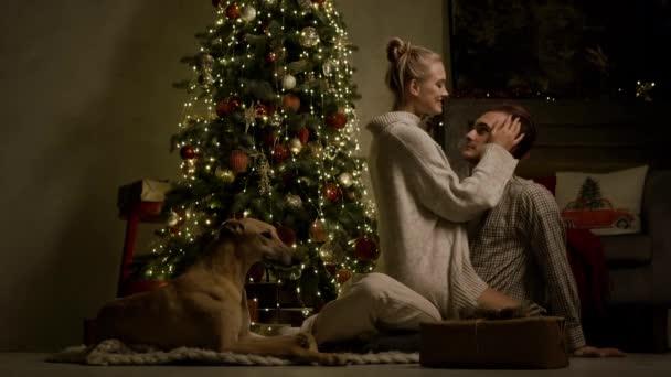 Nový rok. Romantický pár a jejich pes sedí na podlaze v blízkosti vánočního stromu.