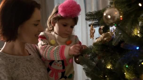 Nový rok. Máma se svou dcerou zdobí vánoční stromeček.