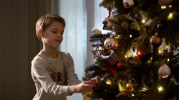 Neujahr. Funny Boy schmückt den Weihnachtsbaum.