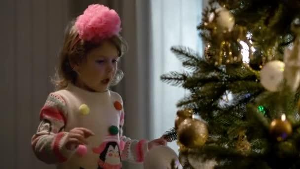 Neujahr. Kleines Mädchen spielt Weihnachtsbaumschmuck, der am Weihnachtsbaum hängt.