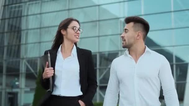 Junge Geschäftsleute auf der Straße. Guy und Girl diskutieren aktiv über Dinge, die die Straße hinunter gehen.