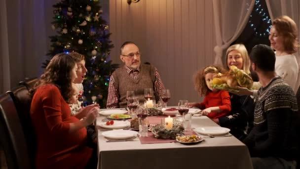 Nový rok. Servírovaný sváteční stůl. Žena slouží kuřecí hlavní jídlo.