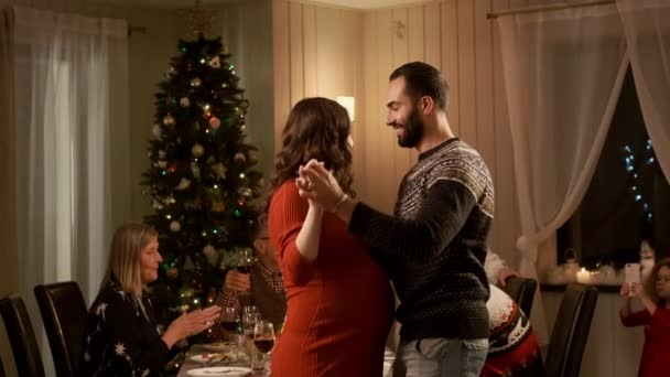 Nový rok. Rodina na sváteční večeři. Příjemná atmosféra. Mladý pár tance