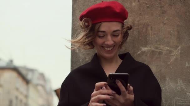 Romantický obrázek dámy v červeném. V jejích rukou mobilní telefon.