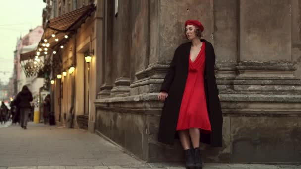 Romantická mladá žena stojící a dotýkající se jí zády proti starověké zdi ve městě.
