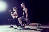 Fotografie Seitenansicht des schönen Sportler und junge Fit Frau zusammen zu trainieren, auf schwarz