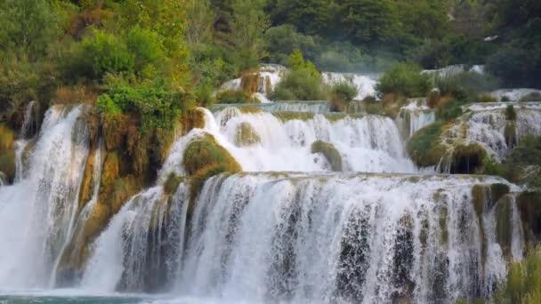 Vodopády Krka, Národní park, Chorvatsko. Krásné potoky pomalu teče v Národním parku Krka mezi stromy a trávou, kaskáda vodopádů. Zpomalené video vody, řeky, potoka, vodopády.