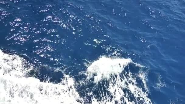 Mořská voda s pěnovým povrchem. Cestování lodí, mořská pěna, pěna na modrém, mořské vlny na pozadí. Hrubá tmavě tyrkysová a modrá Středozemní moře s bílou pěnou. Vodní sprej z lodi. Zpomalené video.