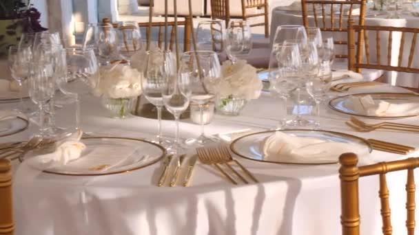 Krásná výzdoba svatebního stolu v bílo-zlatých barvách, na pobřeží, ostrov Hvar, Chorvatsko. Svatba u moře. Zlaté příbory. Krásná svatba. Elegantní nastavení zlatobílého stolu.