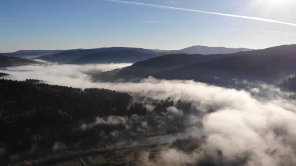 Amazing autumn landscape in Carpathian Mountains. Morning fog over valley and river, coniferous forests on the slopes