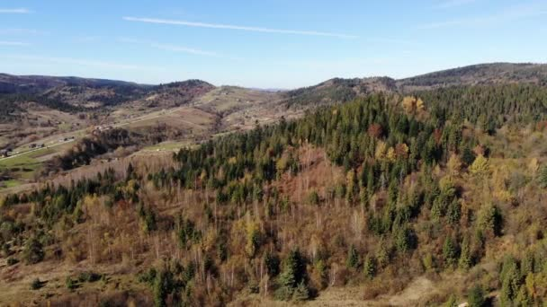 Aerial view of Carpathian Mountains and forests. Village between the mountains. Smooth fly forward