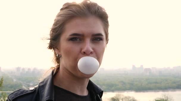 Hravá slečna oblečená v černé kožené bundě stojící izolované nad městem pozadí při foukání bublin s žvýkačky