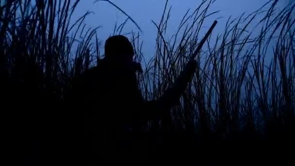 Sziluettjét vadász egy pisztoly puska nádasban