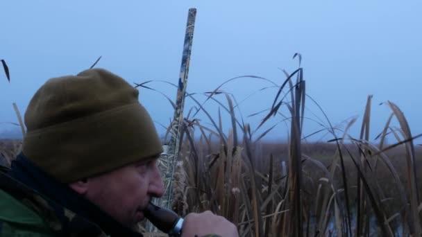 Muž lovec s pistolí v maskování lov na kachny
