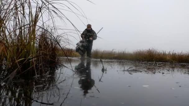 Zpomalený pohyb Hunter s puškou drží několik kachna figuríny