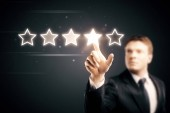 Fotografie blured businessman pointing five star symbol to increase rating of company at dark background