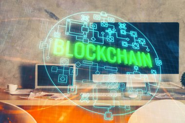 Multi exposure of blockchain theme hologram and table with computer background. Concept of bitcoin crypto currency.