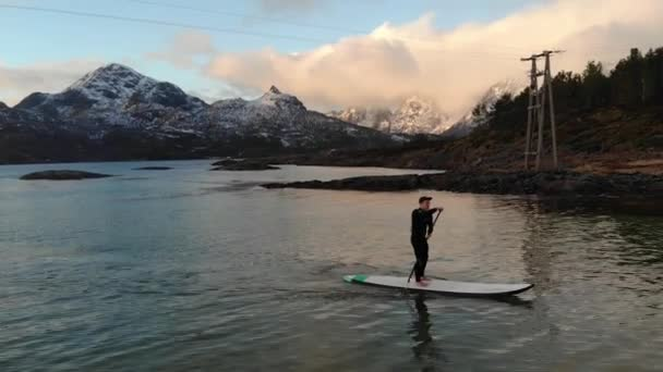 aerial shot slow motion people on sup on the fjord in Norway