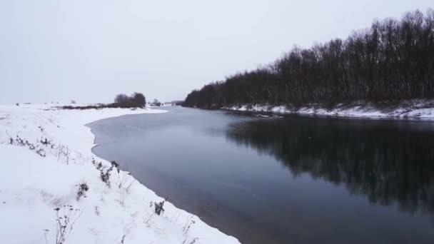 Řeka ve winter parku. Zimní krajina. Sněhové závěje na břehu řeky. Zimní řeka s mlhou.