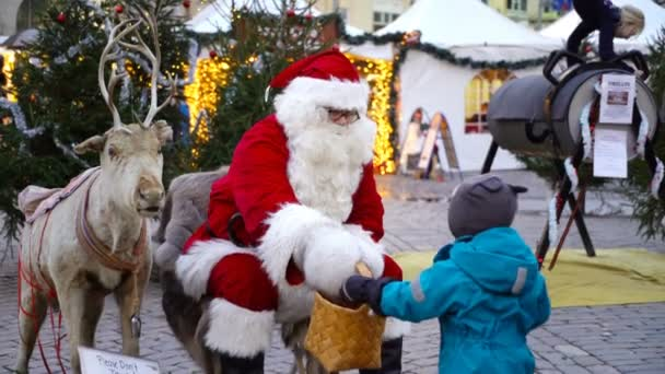 Santa gives gifts to children at the Christmas fair
