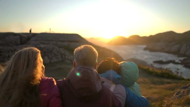 Glückliche Familie bewundert den Sonnenuntergang oder Sonnenaufgang an der felsigen Nordküste des Meeres
