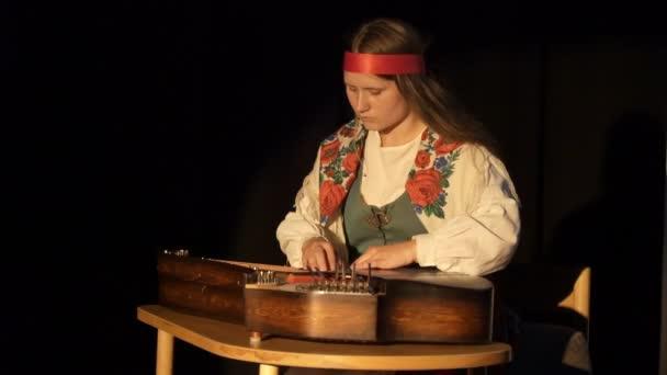 Eine junge Frau in Tracht die Kantele - finnische nationale Saiten gezupft Musikinstrument zu spielen